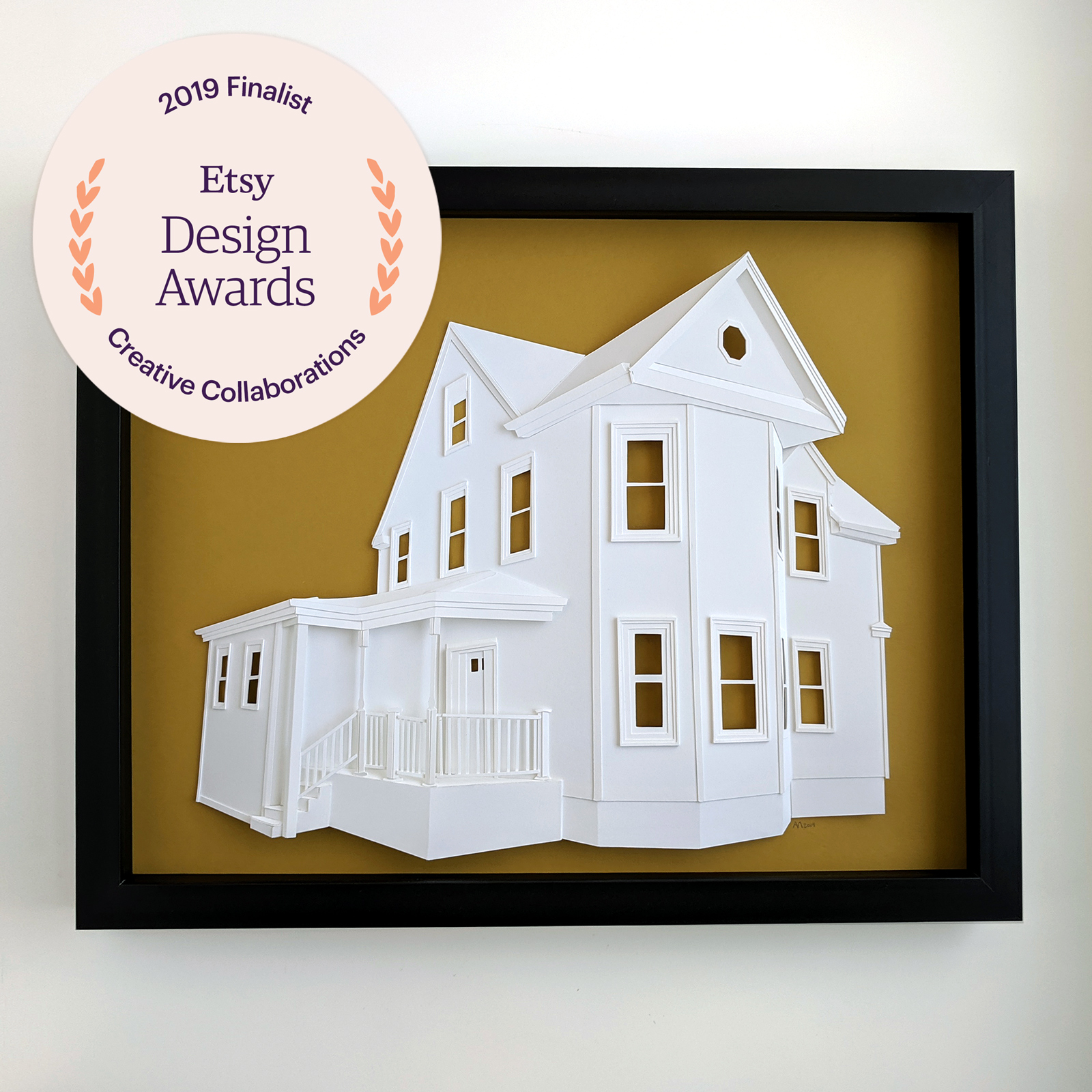 Custom house portrait made of paper depicting a large house with a deep front porch, overlaid with the Etsy Design Awards Creative Collaborations Finalist logo