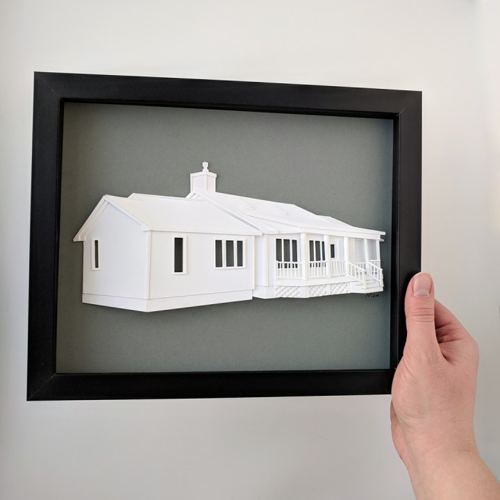 Artist's hand holding a framed paper house portrait