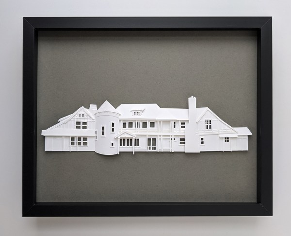 Low-relief paper sculpture of family vacation home made of white paper on a dark gray background in a black frame
