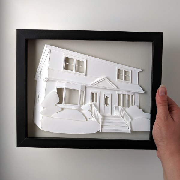 Hand holding a finished, framed house portrait on a light gray background.