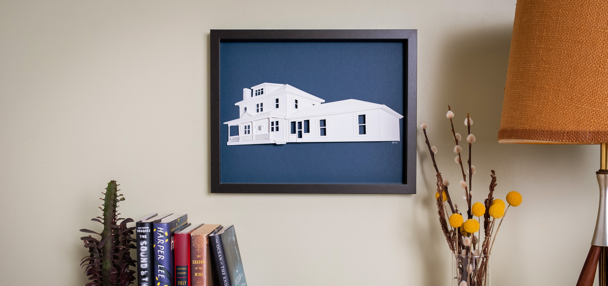 Framed house portrait hanging on a living room wall