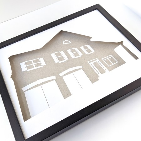 Framed custom house silhouette depicting a 2-story house with double garage, front porch, and sidelights around the front door