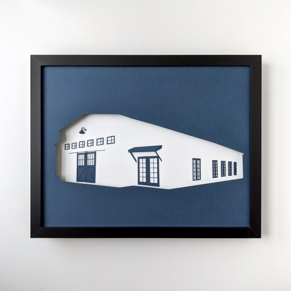 """Framed paper art depicting the """"Making It"""" barn in navy and white."""