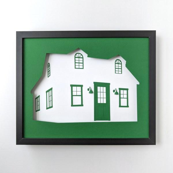 """Framed paper art depicting the """"Making It"""" cottage in dark green and white paper"""