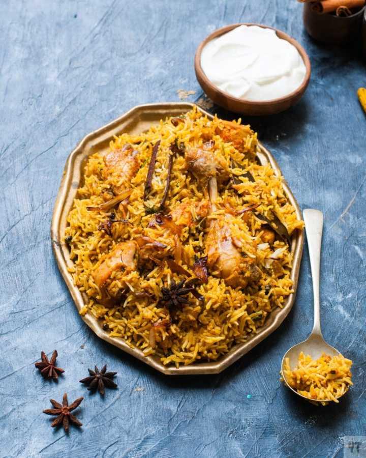 Instant Pot Chicken Biryani on a golden tray with yogurt