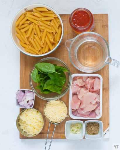 Ingredient shot for chicken parmesan - chicken, cheese,penne pasta, cut onion, garlic,italian seasoning