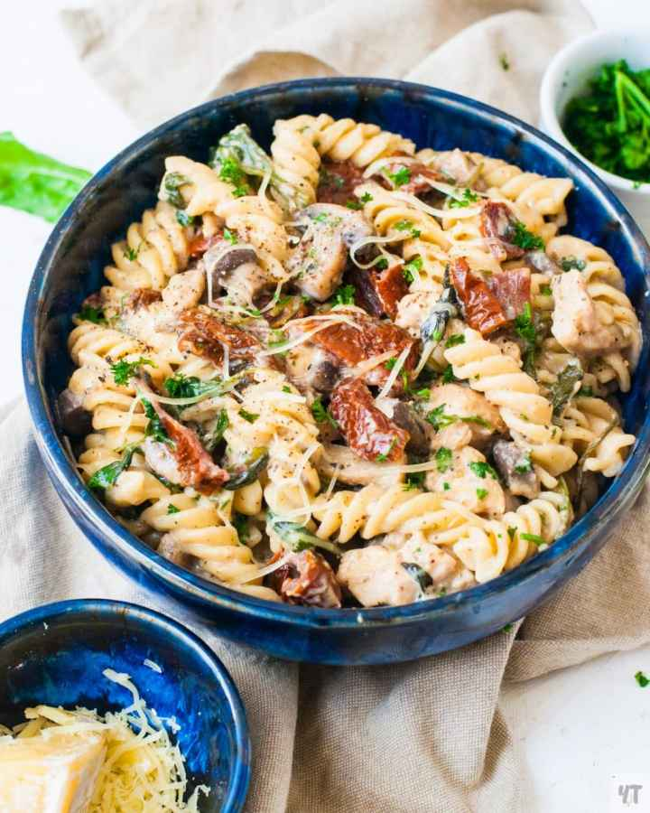 Instant Pot Tuscan Chicken Pasta in blue bowl- Creamy Chicken Pasta with pasta, boneless chicken breast, Sundried Tomatoes,Spinach,Cream Cheese and Parmesan.