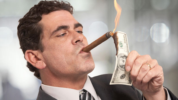 rich-businessman-lighting-cigar-with-100-dollar-bill