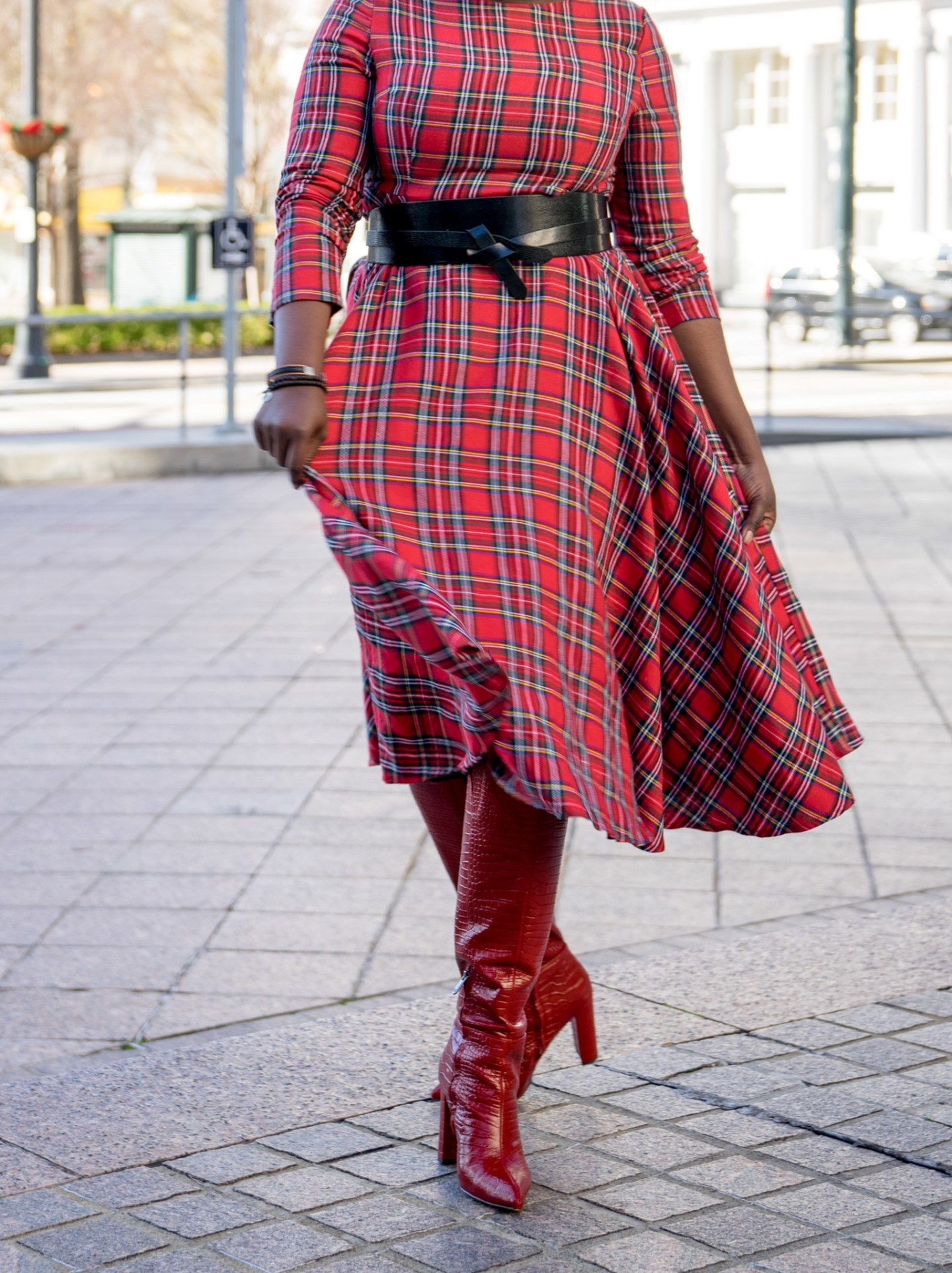 woman wearing red plaid dress and red boots and black belt.