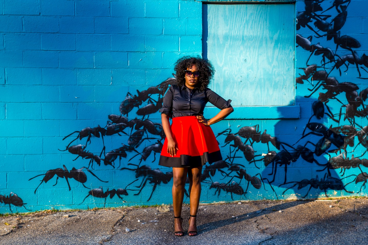 ChiChi wearing a red and black full circle skirt standing in front of an ant mural