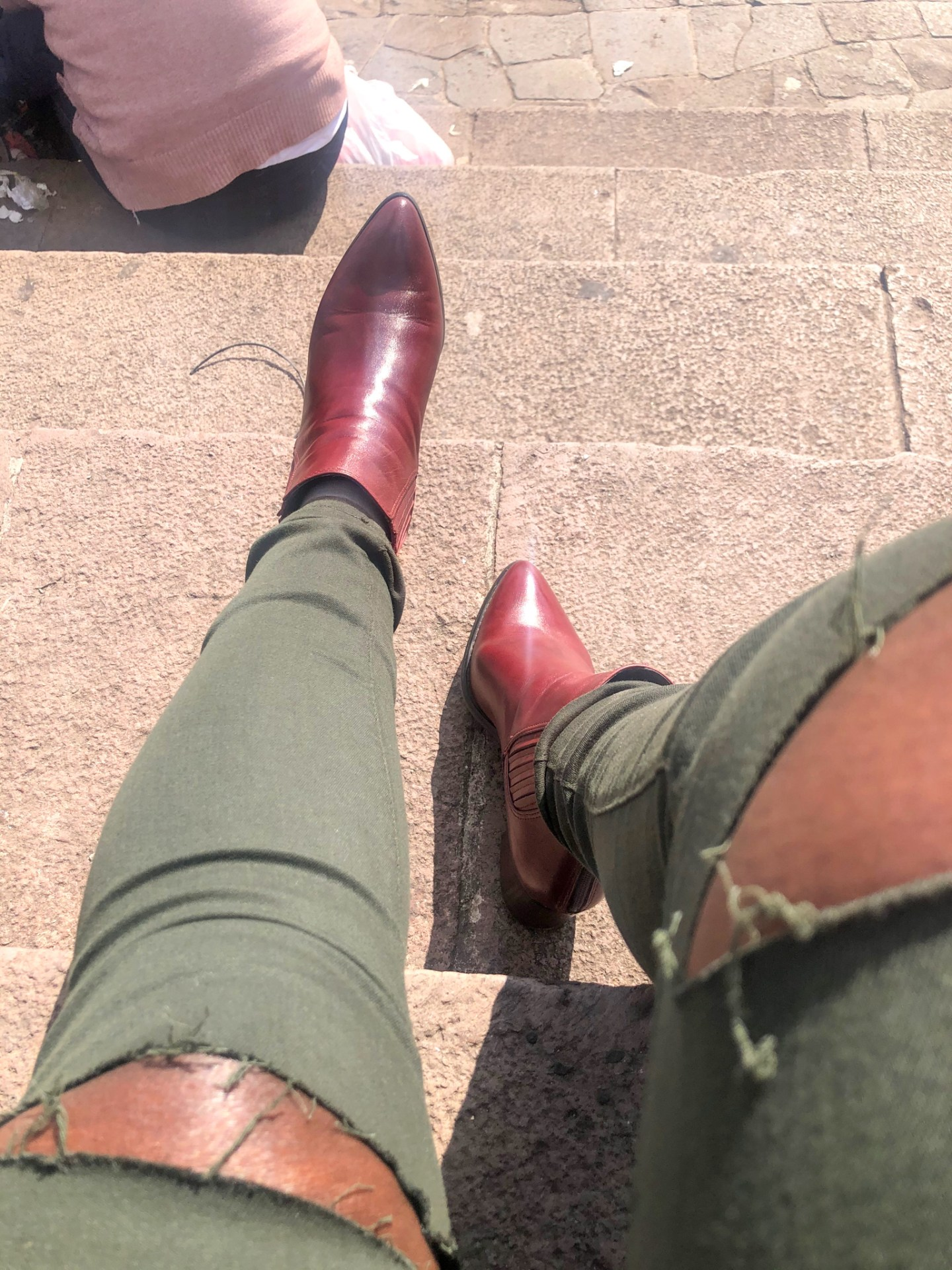 Fashionable jet setter wearing brown chelsea boots in Cusco Peru capitol.