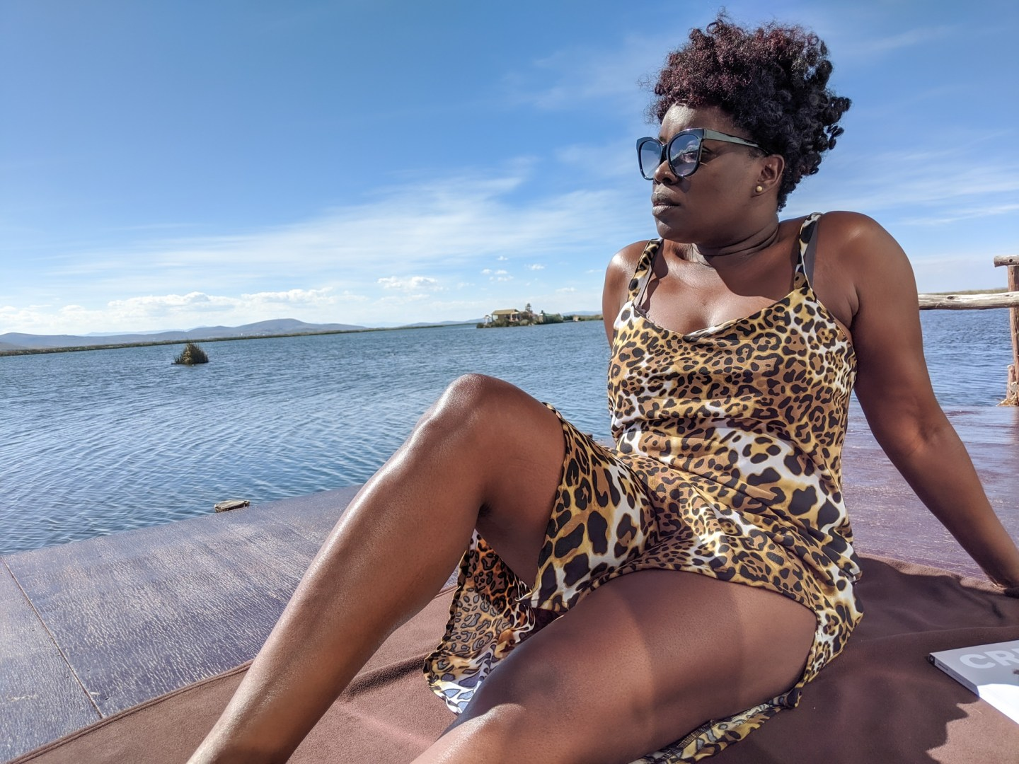 Black travel blogger at the lodge at Lake Titicaca wearing leopard print dress