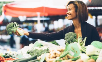 Woman selling vegetables by Shutterstock
