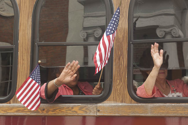 "women with flags waving from ""seniors"" trolley"