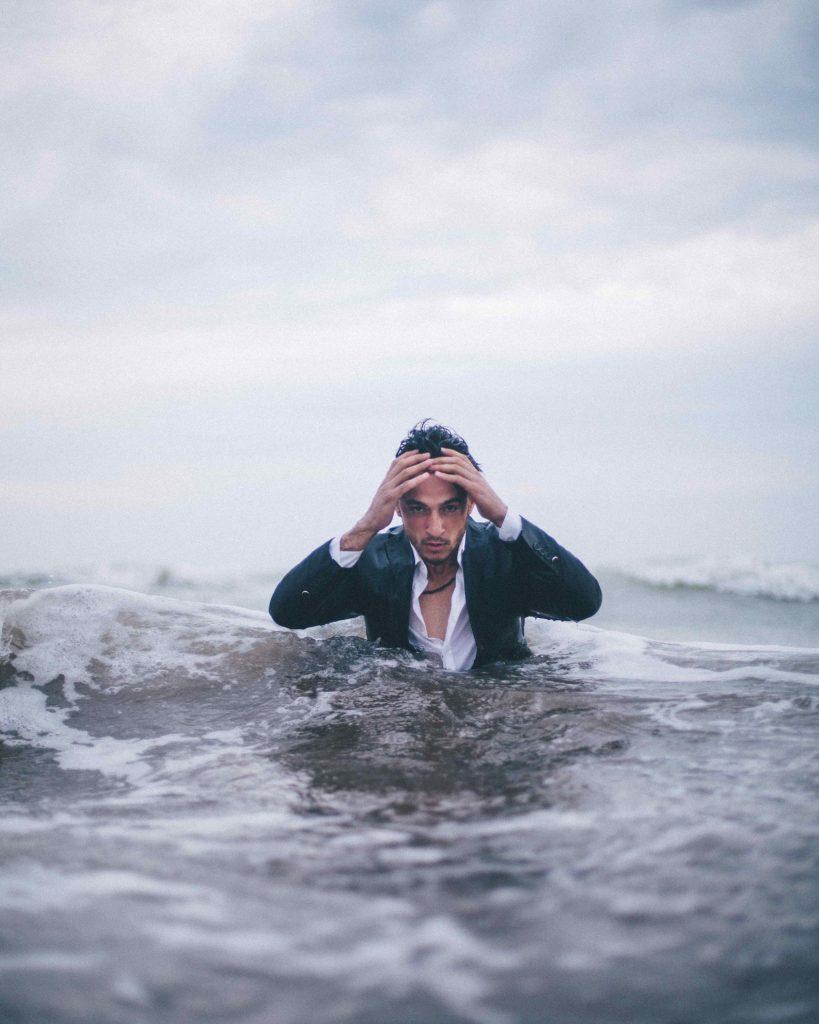 homme dans l'eau submergé qui se prend la tête