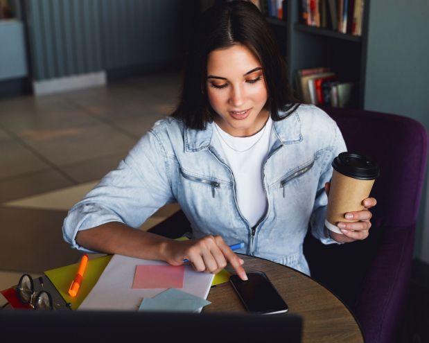 femme qui boit un café et regarde son téléphone