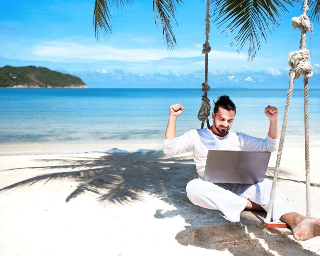 homme sur une balançoire avec un ordinateur sur les genoux