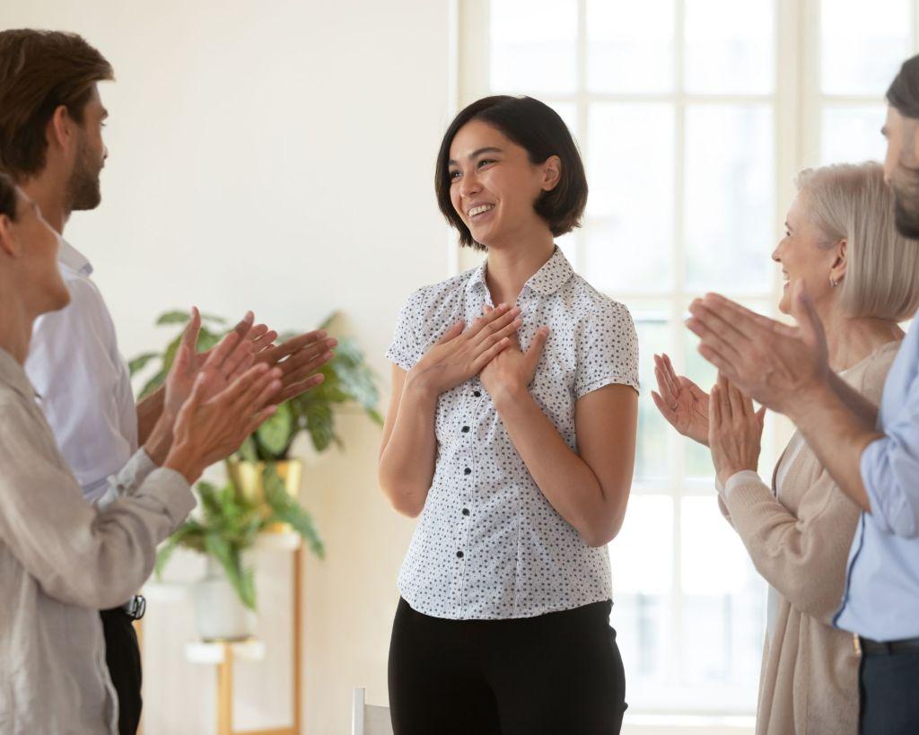 public qui applaudit une femme qui sourit