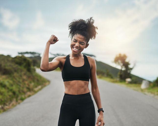 femme sur une route qui montre ses muscles