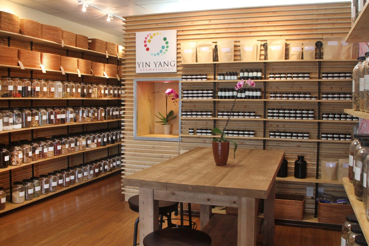 The Yin Yang Dermatology library of herbs: jars and bottles lining clean wooden shelves.