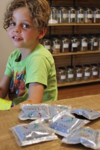A curly-haired child looks over a stack of sealed pouches containing herbal medicine.