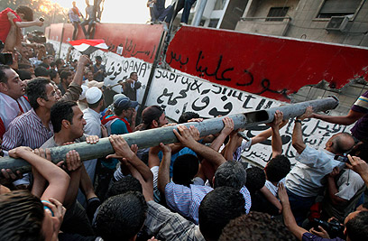 Egyptians demolishing wall outside embassy (Photo: Reuters)