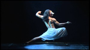 Black background with dancer light by blue light in a sideways lunge with mask on face
