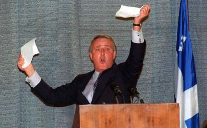 The photo depicts Prime Minister Brian Mulroney holding up pieces of paper he had torn during a speech in Sherbrooke, Quebec, on Sept. 28, 1992.
