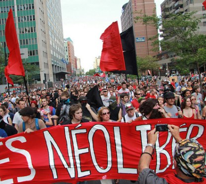 """The photo depicts the successful 2012 student strike in Quebec against austerity policies at universities. At the front of the photo we can see students holding a big red sign that allegedly reads """"les neoliberales"""", and a huge crowd of people following them with big red flags."""