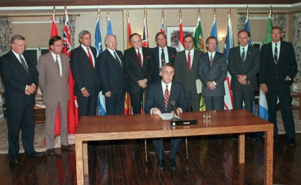 The photo depicts the Prime Minister Brian Mulroney who sits at the table and reads a statement after he and the provincial premiers, who stand behind him, reached an agreement in principal on constitutional grievances, after meeting at Meech Lake, April 30, 1987.