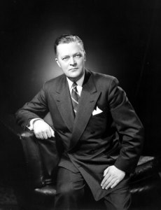 The photo depicts Jean Lesage- a leader of the Liberal Party of Quebec, who served as a premier of Quebec from 1960 to 1966, and is often viewed as the father of the Quiet Revolution- sitting down on a couch and posing for a picture.