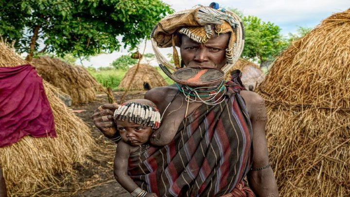 Ethiopian Mursi Tribe Women with her baby in lap