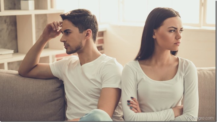 Couple is having a quarrel while sitting on sofa at home.