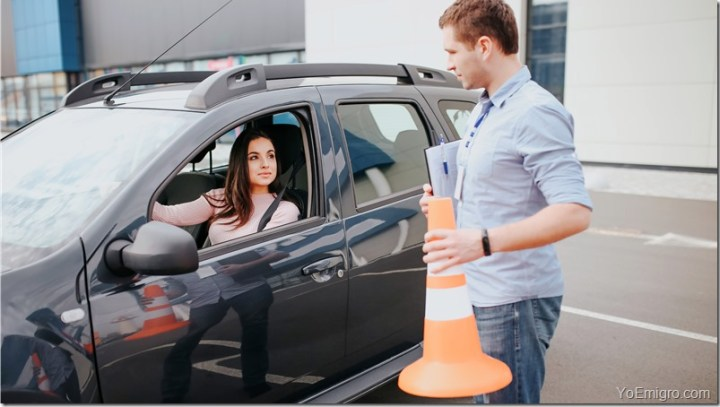 Male auto instructor takes exam in young woman. Stand outside of car with orange sign in hands. Look at woman in car. Female studenthold hands on steering wheel adnd look at instructor.