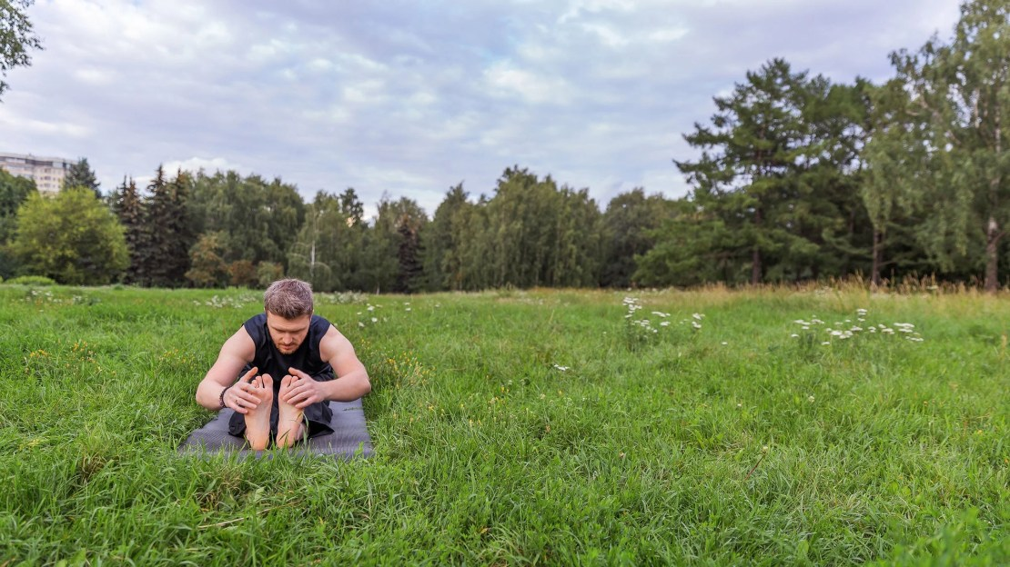 A person rests in Seated Forward Fold in a grassy field