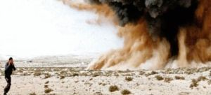 A-rebel-holds-his-ears-as-a-bomb-explodes-in-the-desert-near-Brega