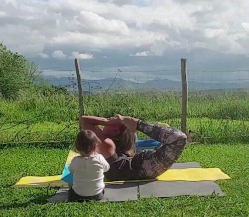 yoga avec enfant qui regarde la posture de l'arc