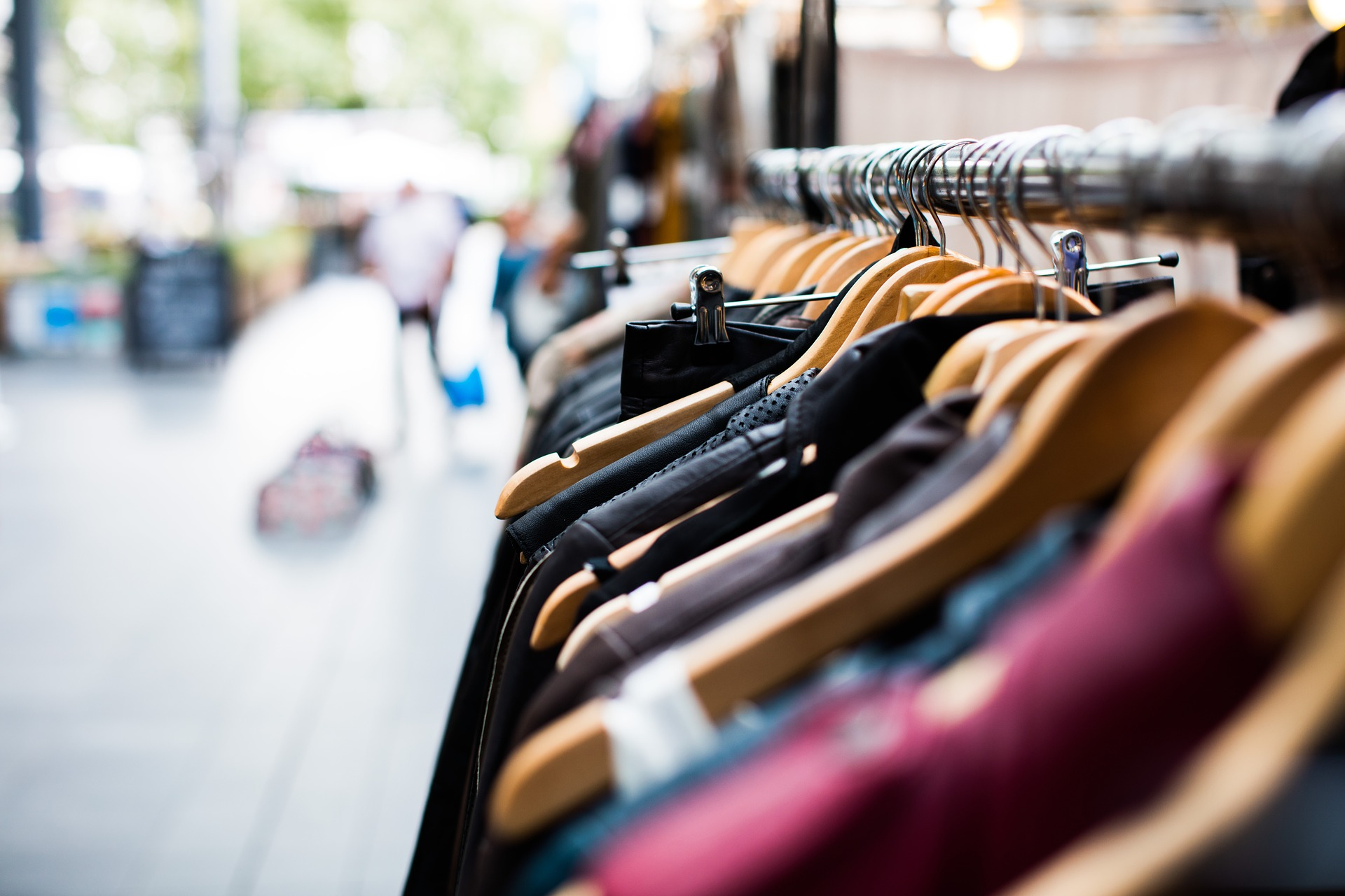An assortment of clothes are displayed on hangers on a rack outside, pointing towards an open sidewalk ahead.