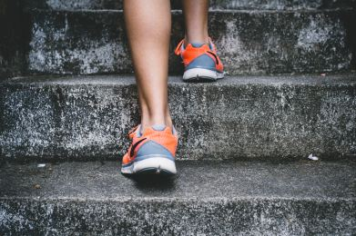 A person wearing running shoes climbs a flight of stairs determinedly