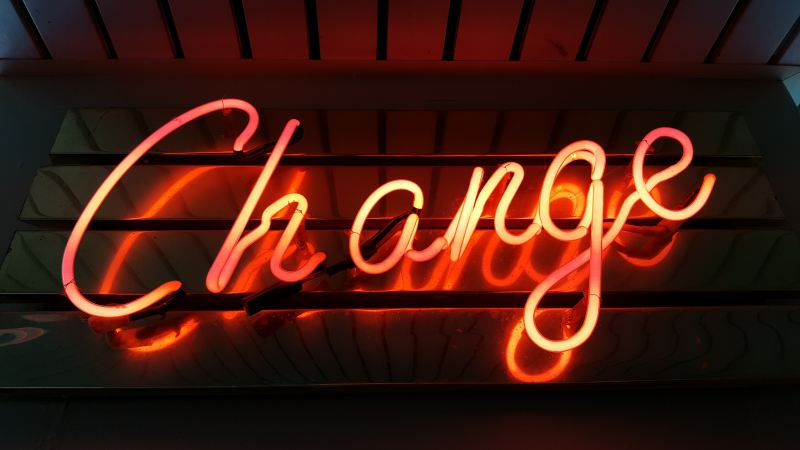 """A warm colored orange and red neon sign in cursive letters says """"Change"""""""