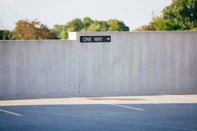 """A wide open parking lot sports a sign dictating """"One-Way"""" is the only direction allowed"""