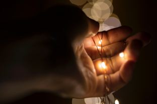 A hand holds three small lights in its palm