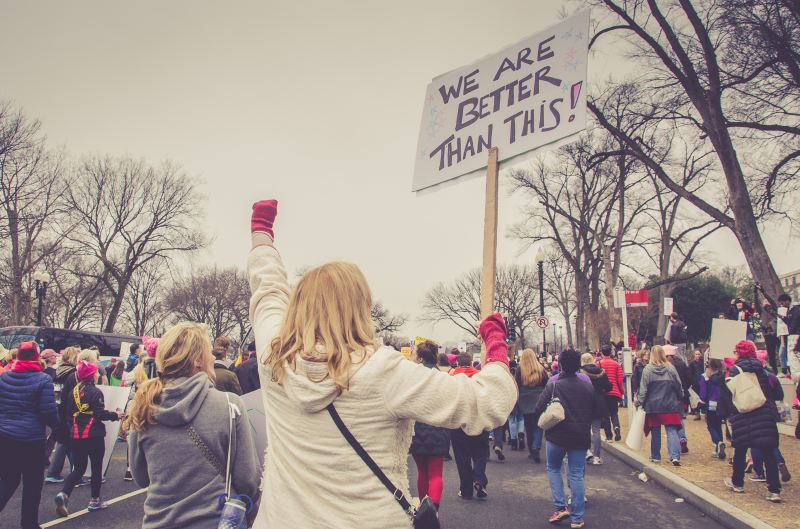 """A woman at a protest rally holds her fist in the air and a sign that says, """"We Are Better Than This!"""""""