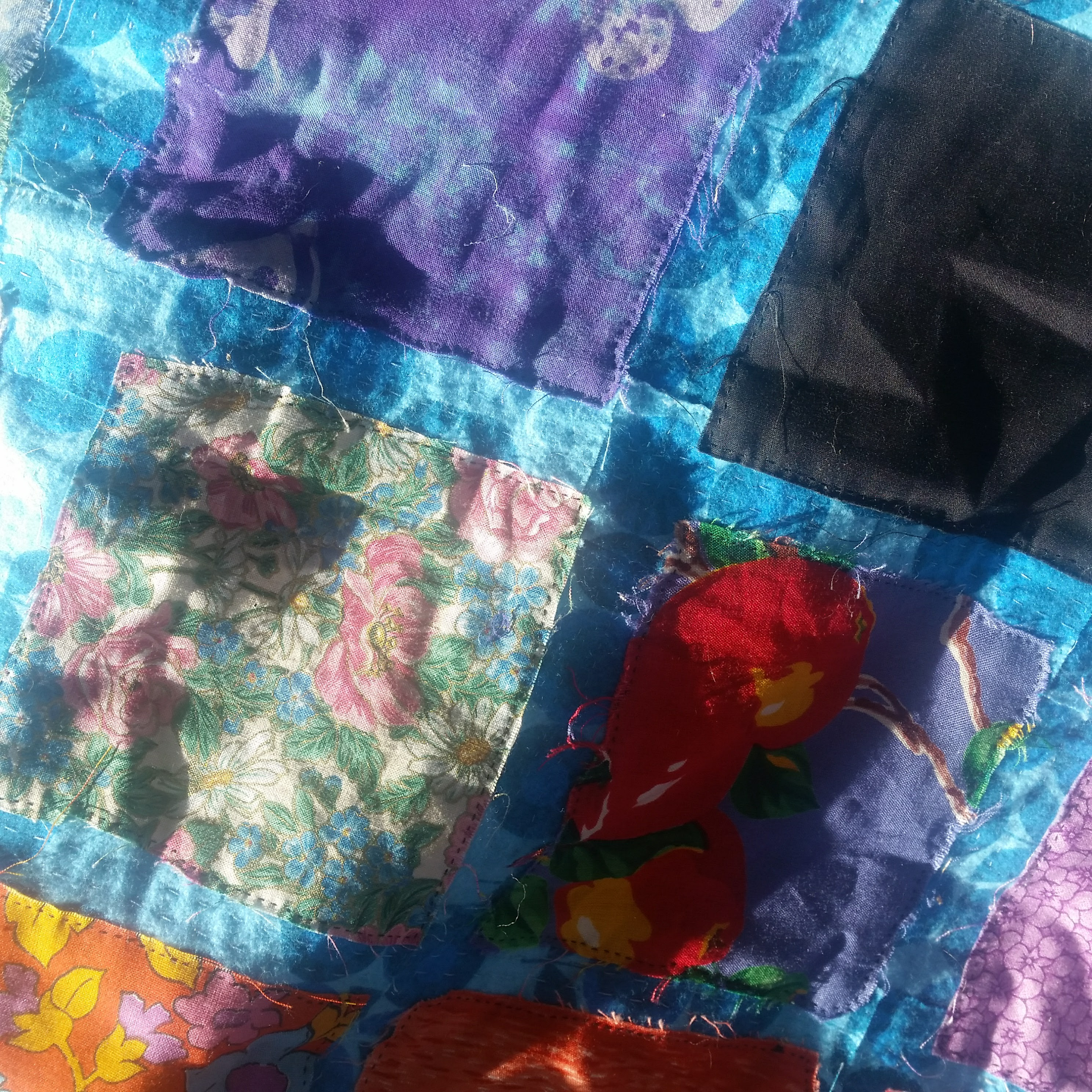 The handmade quilt I made during my abusive relationship sits in the sun, in shades of blue, purple, green, and pink.