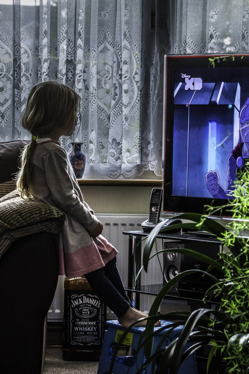 A little girl stands transfixed in front of her television.