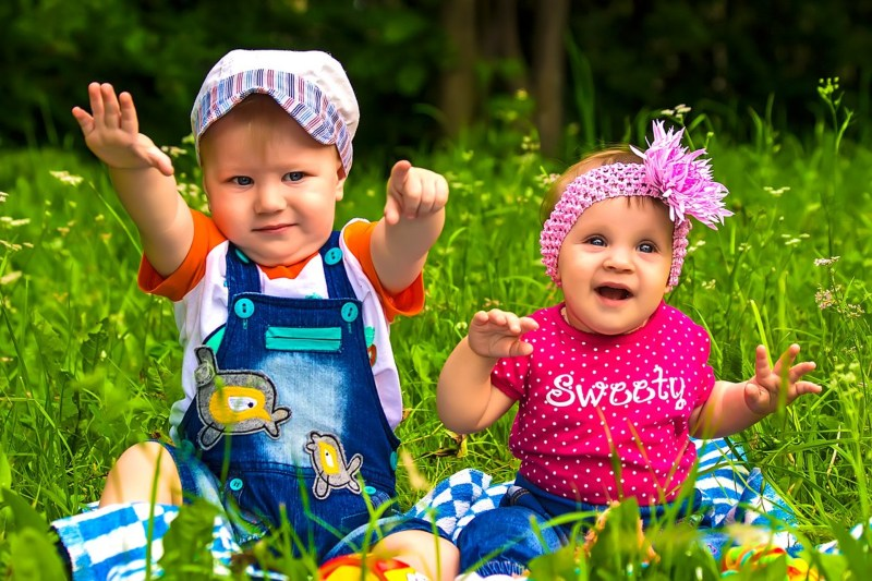 Two toddlers play together, one wearing all blue boy-coded clothing, the other wearing all pink girl-coded clothing.