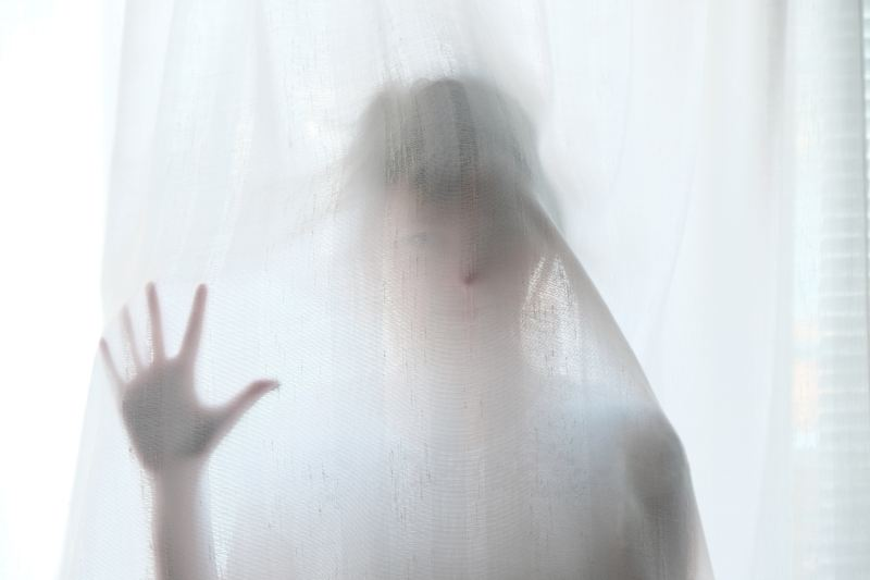 A person stands behind white sheets looking almost invisible in a ghostly way.