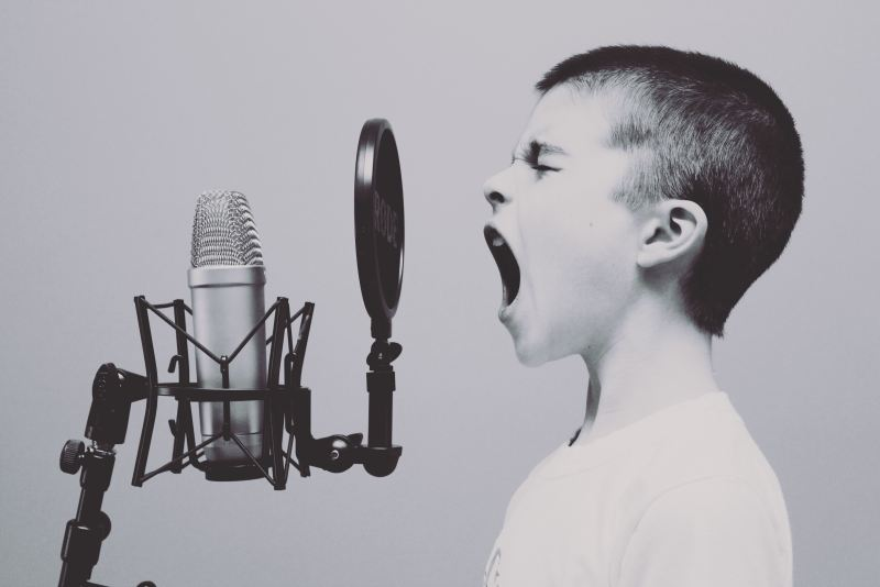 A boy opens his mouth as loud as possible to shout into a microphone.