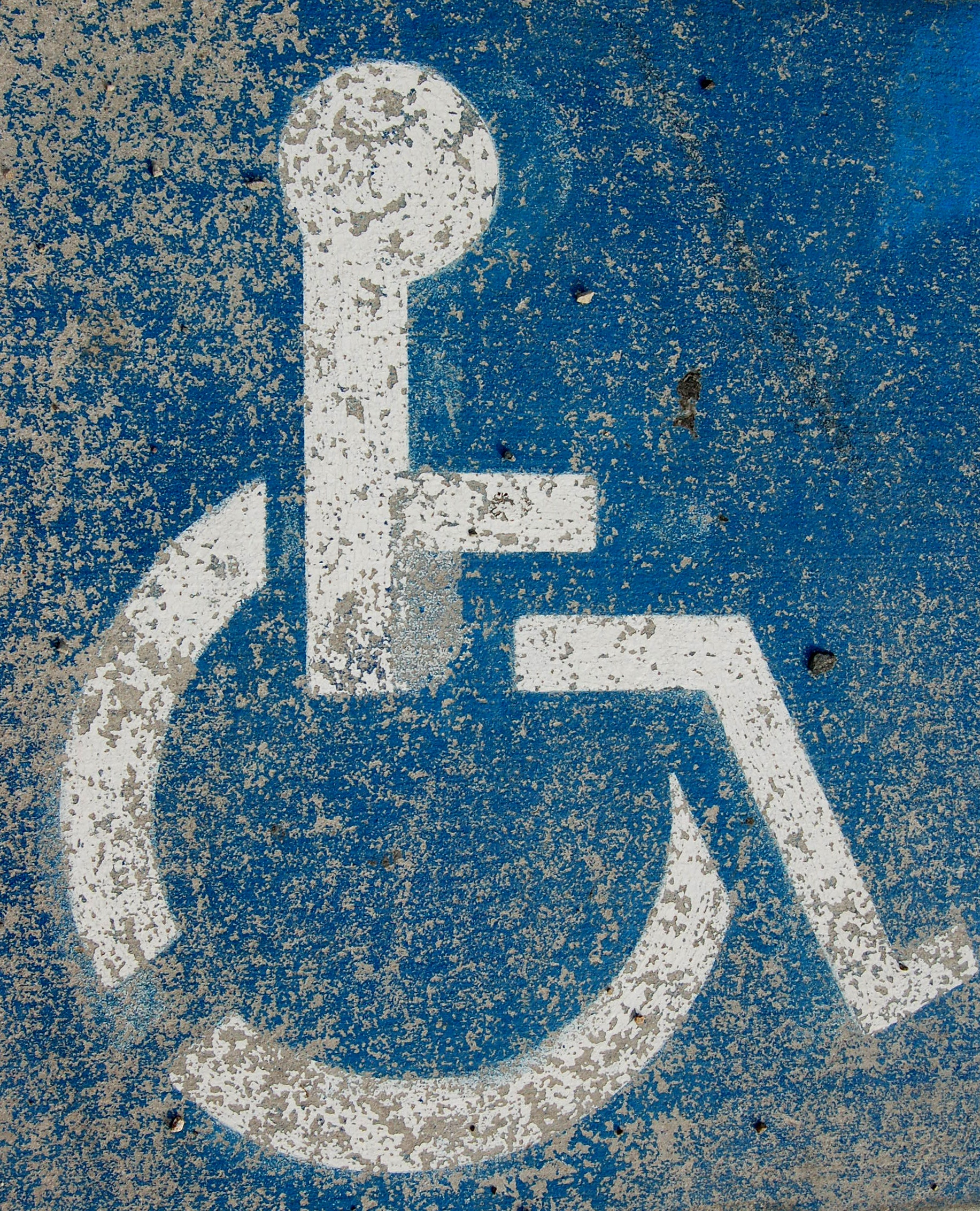 A disability parking spot is run down and worse for wear.