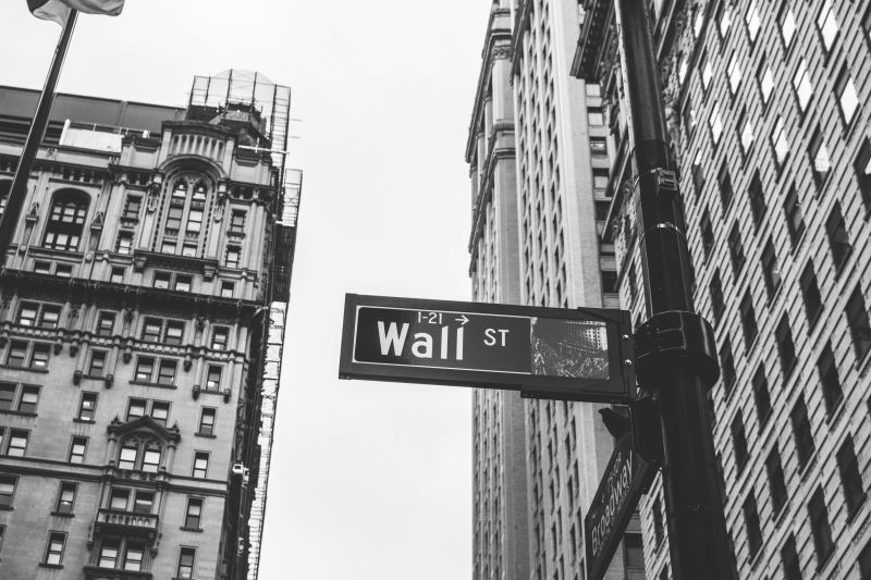 A street sign pointing the wall to Wall Street, home of most of the nations's financial power.